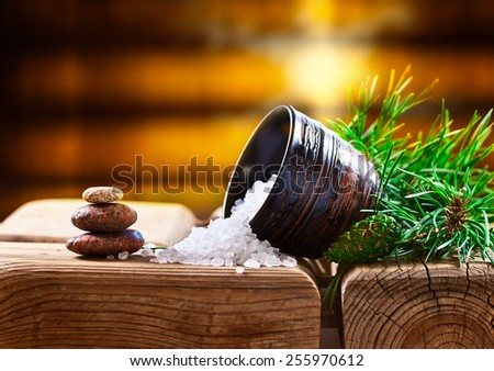 Sea salt with coniferous aroma on an old wooden table - stock photo