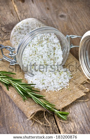 sea salt with dry rosemary in a glass jar, a branch of fresh rosemary on a wooden background - stock photo