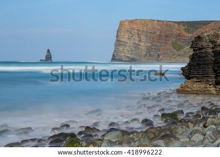 Sea scape stone needle. Portugal Aljezur Algarve, long exposure. - stock photo