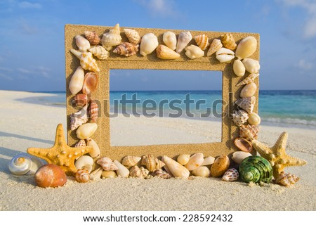 Sea shell sand frame by the beach. - stock photo