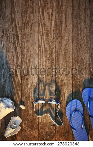 sea shells, goggles and sandals on a dock - stock photo