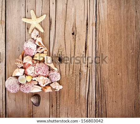 Sea shells shaped as a Christmas tree on a rustic wooden background - stock photo