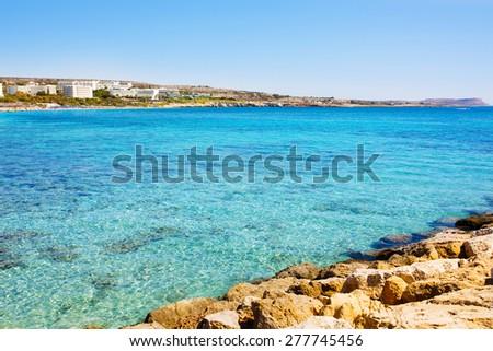 Sea shore. Turquoise sea water of Cyprus coast. Agia napa beach. Hotels view. - stock photo