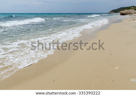 Sea shore view with white waves and sand