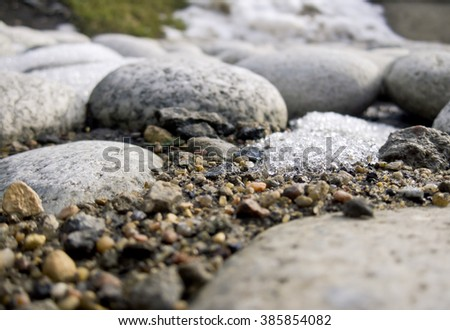 Sea stones on the wet ground melts the snow come spring there is green grass in the background