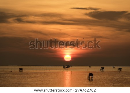 sea sunset with Fishermen's cottages Cabin - stock photo
