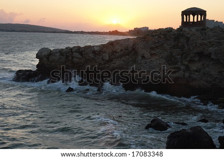 Sea surf great wave break on coastline and cape with pavilion at a distance - stock photo
