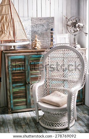 sea travel styled shabby chic interior corner with map wicker chair ship and shell  - stock photo