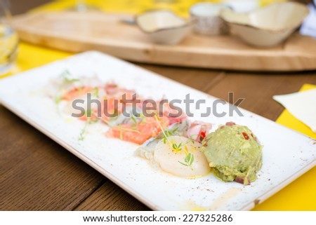 Sea trout, scallops and shrimps with citrus-pickled onions, guacamole and cilantro   on the plate. Shallow DOF - stock photo