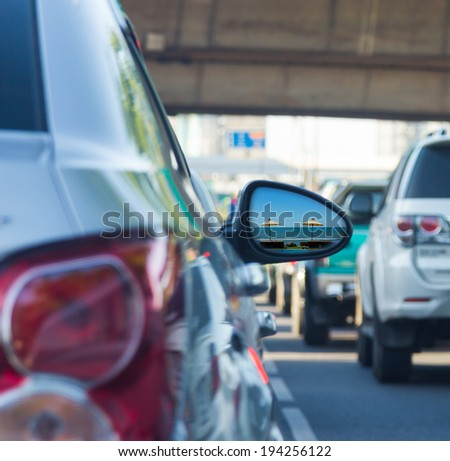 Sea view in side mirror of car with traffic jam - stock photo