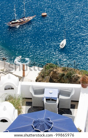 Sea view on moored yacht and sailboat as seen from the restaurant'??s terrace on cliff Santorini luxury island, Greece - stock photo