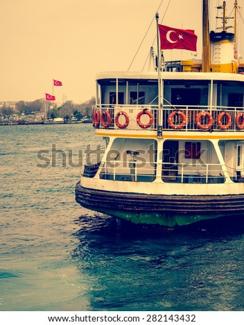 Sea voyage to Bosporus on the old ferryboat, Istanbul's water transport. Turkish steamboat with flag at sunset. Vintage passenger ship - travel concept of Turkey in retro style. - stock photo