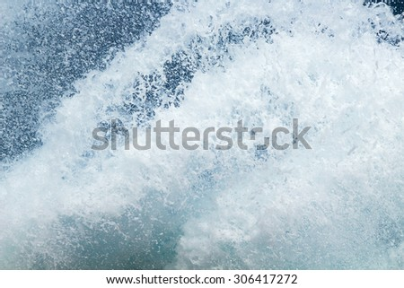 sea water foam flying against the backdrop of blue water - stock photo