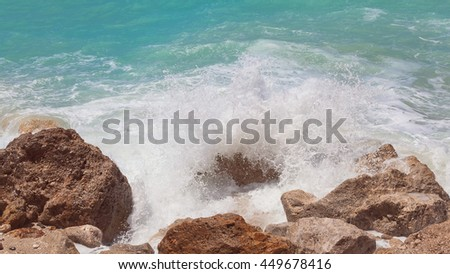 Sea water splashes on the rock, close up.Scenic view of waves breaking against rock on summer day. Vintage toned image - stock photo