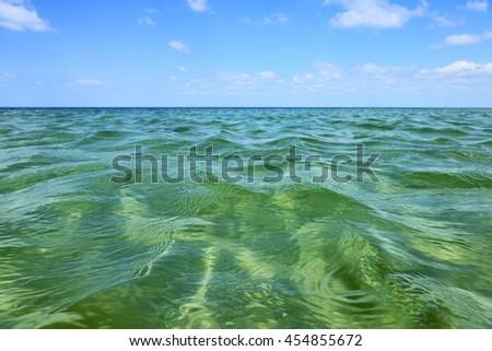 Sea water under blue sky. Water surface as texture or background. - stock photo
