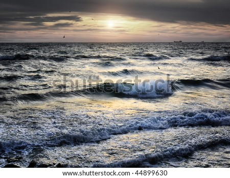 sea wave and sunset with birds and ships at background - stock photo