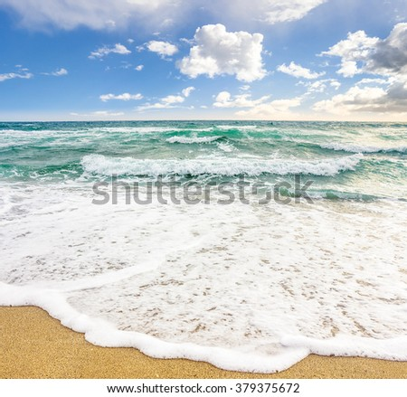 sea wave attacks the sandy beach and break on them
