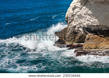 Sea wave breaking on a big rock on the beach - stock photo
