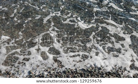 Sea wave incident on a pebble beach, wide image, 16 9 ratio - stock photo