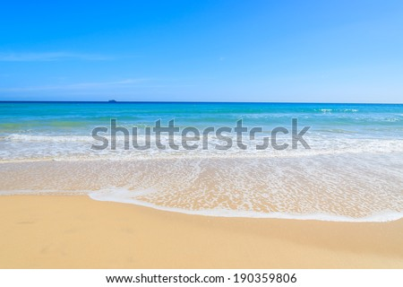 Sea wave on beach with golden sand and turquoise crystal clear water on Jandia peninsula, Morro Jable, Fuerteventura, Canary Islands, Spain  - stock photo