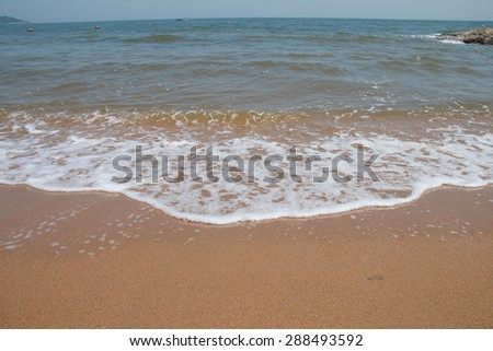 Sea wave over sand beach
