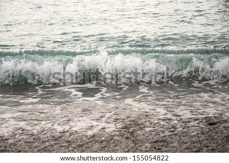 Sea waves and pebble beach in black and white - stock photo