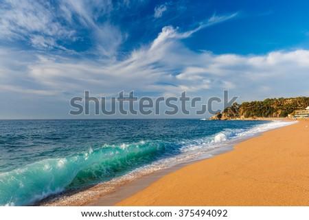Sea waves and sand main beach at popular holiday resort Lloret de Mar on Costa Brava in the morning , Catalunya, Spain - stock photo