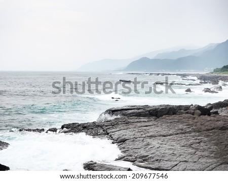 Sea waves crashing against the rocks - stock photo