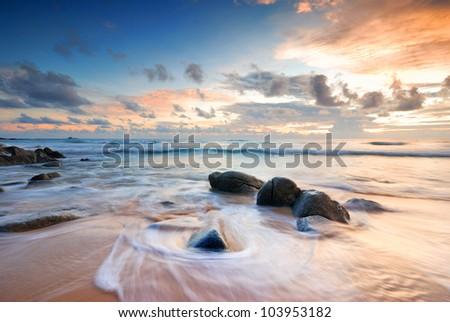 Sea waves lash line impact rock on the beach - stock photo