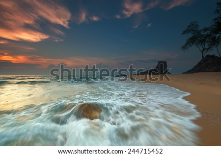 Sea waves lash line impact rock on the beach with beautiful sunrise  (soft focus, shallow DOF, slight motion blur)  - stock photo