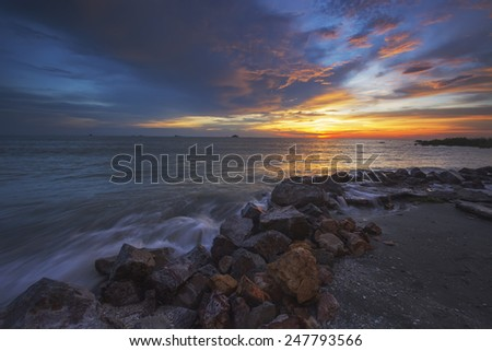 Sea waves lash line impact rock on the beach with beautiful sunrise  (soft focus, shallow DOF, slight motion blur)