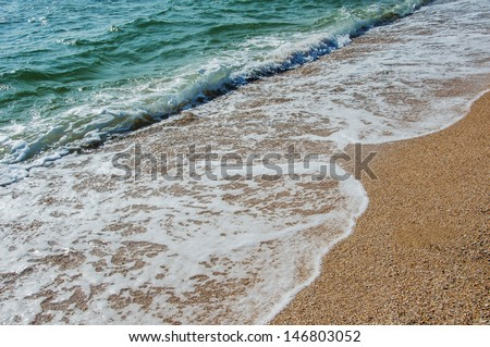 Sea waves run over on the shore and leave a trail of foams