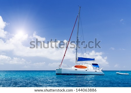 Sea yacht in azure water. Blue sky and green tropic island. Seychelles.