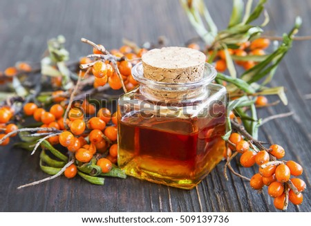 Seabuckthorn oil bottle with berries branches