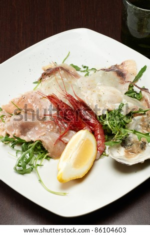 seafood appetizer with oyster, shrimp and arugula - stock photo