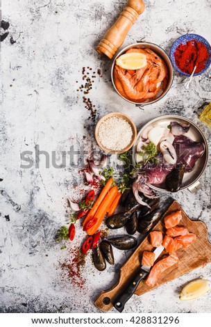 Seafood assortment. Overhead shot of raw scallops, fish, shrimps and mussels with lemon and spices on crushed ice. Preparing recipe food concept. - stock photo