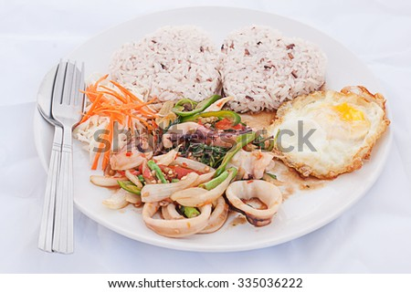 Seafood curry (stir basil) and fried egg over rice with fish sauce , Thai food - stock photo