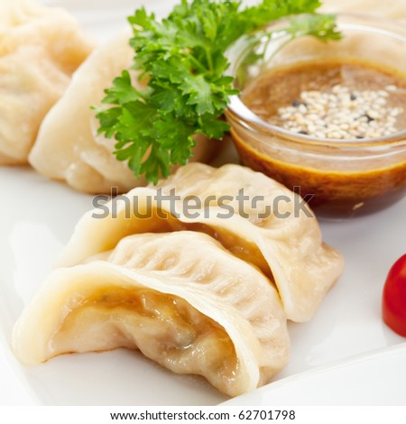 Seafood Dumpling - Gyoza. Garnished with Sauce, Tomato and Parsley