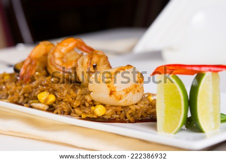 Seafood Fried Rice with Shrimp and Scallops and Garnish on Plate - stock photo