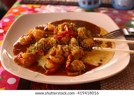 seafood lunch in red curry sauce squid prawn octopus with chinese sticks and fork in the plate on the table - stock photo