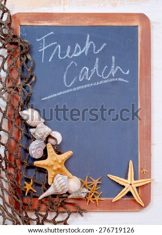 Seafood menu image of blackboard with fishnet and seashells and starfish gathered on left. The slate on the blackboard is rough and the brown frame is worn. Message is fresh catch with copy space - stock photo