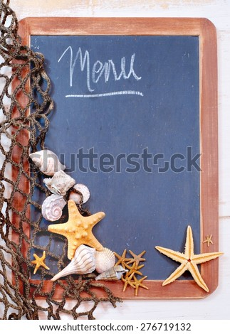 Seafood menu image of blackboard with fishnet and seashells and starfish gathered on left. The slate on the blackboard is rough and the surrounding brown frame is worn. Message is menu with copy space