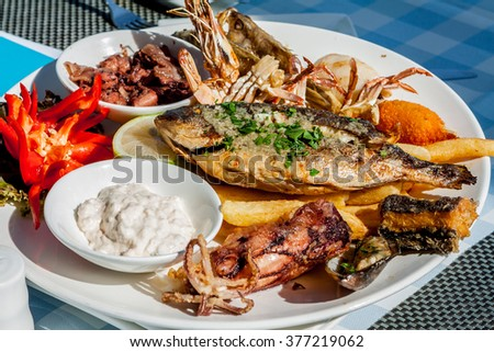 Seafood on the plate with sauce - stock photo