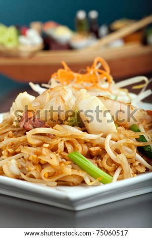 Seafood pad Thai dish of fried rice noodles on a square white plate with chopsticks and grated carrot garnish. Shallow depth of field. - stock photo
