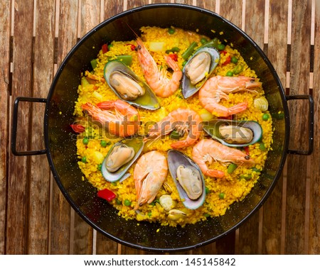 Seafood Paella in black pan  -traditional spanish rice dish - stock photo