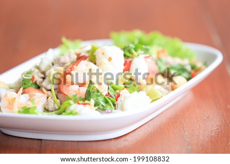 Seafood salad on wooden table - stock photo
