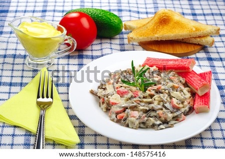 Seafood salad with crab sticks on a blue tablecloth - stock photo
