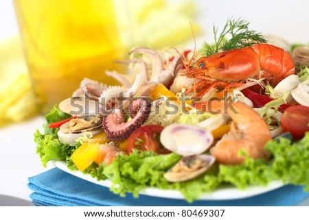 Seafood salad with shrimp, clams, octopus tentacles, calamari rings and prawns with a variety of vegetables with white wine in the back (Selective Focus, Focus on the shrimp on top of the salad) - stock photo