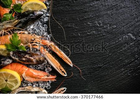 Seafood served on black stone - stock photo