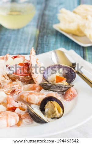 Seafood stew made with lobster, crab, shrimp and clams cooked in coconut milk with tomatoes and onions - stock photo